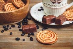 Tam są ciastka, cukierek, Czekoladowi grochy, maczek; Porcelana spodeczek i nakrętka z Coffe, Smakowity Słodki jedzenie na Drewn Obrazy Stock