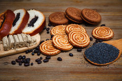 Tam są kawałki rolka z poppyseed, ciastka, Halavah, Czekoladowi grochy, Smakowity Słodki jedzenie na Drewnianym tle Obrazy Stock