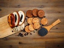 Tam są kawałki rolka z poppyseed, ciastka, Halavah, Czekoladowi grochy, Smakowity Słodki jedzenie na Drewnianym tle, Odgórny wid Zdjęcie Stock