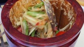 Tam vert de préparation de som de salade de la papaye des femmes thaïlandaises en mortier en bois avec le pilon Fin vers le haut  clips vidéos