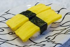 Tamagoyaki Sushi or Sweet Omelet with Rice in Plate. Tamagoyaki. Sushi or rice with egg topping in Japanese food stock image