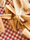 Tamale Husk Trimmings. Corn husk remnants and trimmings of ends on a red and white checkered tablecloth. Image represents holiday meal traditions in the Hispanic Royalty Free Stock Photography