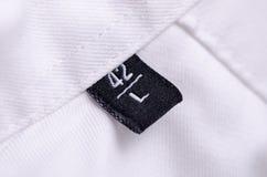 Tamanho macro L da etiqueta da camisa branca imagem de stock