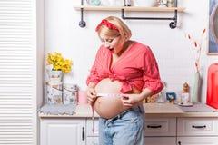 Tamanho positivo Mulher gravida surpreendida agrad?vel que guarda a medida de tipo e que usa a em sua barriga ao expressar a mara imagem de stock