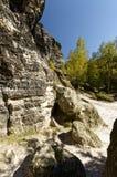 Tamanhos variados das rochas na terra e de penhascos altos ao lado dele com as árvores no fundo Imagem de Stock