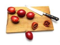 Tamarilli sul tagliere di legno con il coltello immagine stock