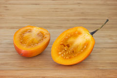 Tamarillo cut in half on a chopping board Stock Photos