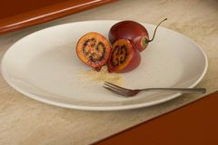Tamarillo sliced mouthwatering. Two Tamarillo , one cut in half with Brown Sugar for added taste. On a white plate with desert Fork Royalty Free Stock Photo