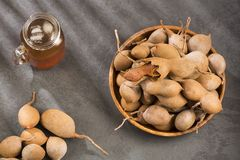 Tamarind juice in a glass surrounded by fresh ripe tamarinds - Tamarindus indica royalty free stock photo
