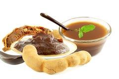 Tamarindfrukt med trämassa eller deg för chutney för koncentrat för tamarindfruktvattenfruktsaft på vit bakgrund arkivfoto