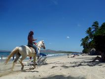 Tamarindo Beach Costa Rica. Local man gallops accross the white sand beach while drinking a beer at Tamarindo Costa Rica Royalty Free Stock Photos