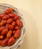 Tamato in woody basket. On wood table stock photo