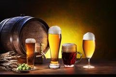 Tambor de cerveja com vidros de cerveja em uma tabela de madeira. Imagens de Stock