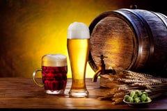 Tambor de cerveja com vidros de cerveja em uma tabela de madeira. Imagem de Stock