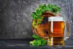 Tambor de madeira da cerveja do ofício com caneca e os lúpulos de vidro na adega escura foto de stock royalty free
