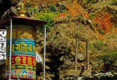 Tambor del Nepali del rezo en una trayectoria de la montaña cerca del templo budista imagen de archivo libre de regalías