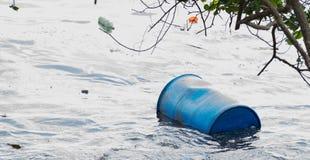 Tambor plástico que flota en el lado de la playa y el otro plástico que fluye Imagen de archivo libre de regalías