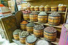 Tambores das especiarias e das leguminosa para a venda colocada em prateleiras para a venda em um souk Fotos de Stock