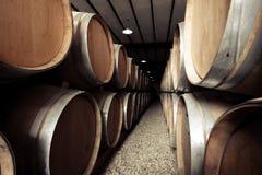 Tambores de vinho empilhados na adega velha da adega Efeito retro do vintage Foto de Stock