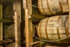 Tambores do bourbon do carvalho na cremalheira no armazém imagens de stock royalty free