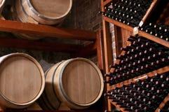 Tambores e garrafas de vinho na prateleira em uma adega Imagens de Stock Royalty Free