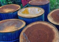 Tambores industriais azuis que oxidam em um cemitério de automóveis Fotos de Stock Royalty Free