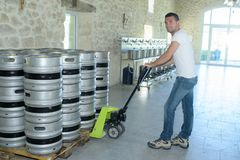 Tambores moventes do trabalhador com caminhão de pálete fotos de stock