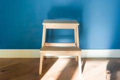 Tamborete de madeira da escada do pas-de-deux com fundo matte azul da parede foto de stock
