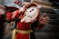 Tambour de basque musical dans les mains d'un homme habillé dans les gens images stock
