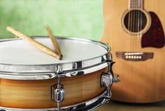 Tambour de piège et guitare acoustique sur un fond vert Photos libres de droits