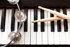 Tambourine and drum sticks on piano key. Royalty Free Stock Photography
