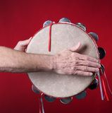 Tambourine Played On red. A tambourine being played isolated against a red background in the square format with copy space Stock Photos