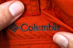 Embroidered logo Columbia on red clothes in person hands. Royalty Free Stock Photography