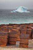 Tamburi arrugginiti sulla costa artica con l'iceberg su fondo Immagine Stock