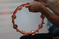 Tamburin, das in den musikalischen Händen gespielt wird Lizenzfreies Stockfoto