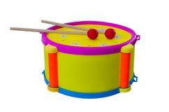 Tamburo con il children& x27 dei bastoni; strumento musicale di s isolato su un fondo bianco Fotografia Stock