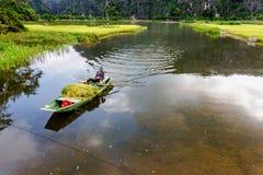 TAMCOC, NINHBINH, ВЬЕТНАМ - 25-ое мая 2014 - неопознанный человек плавая шлюпка риса на потоке Стоковые Фото