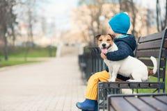 Tamdjurbegreppet med pojken som kramar hans husdjurhund i vår, parkerar royaltyfri bild