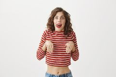 Tame me. Studio shot of funny childish woman acting like dog with palms over chest and sticking tongue, looking with. Popped eyes at camera while standing over Royalty Free Stock Photography