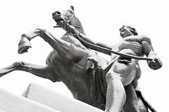 Taming of Horses. One of the famous Taming of Horses public ensemble by Klodt at Anichkov Bridge in St. Petersburg. Russia, while snowing Stock Photography
