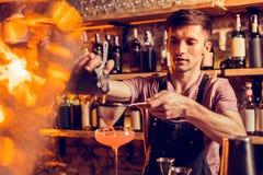 Tamis complet de versement de jus de barman tout en faisant le cocktail photo libre de droits