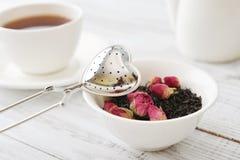 Tamis de thé et bourgeons roses Images stock