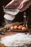 Tamisage de la farine d'un tamis sur une table en bois Images libres de droits