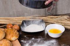 Tamizar la harina para el pan Fotografía de archivo libre de regalías