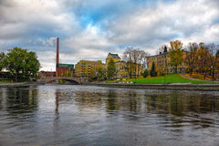 Tammerkoski embankments in Tampere. Fall colors and old factory building of red brick on  embankments channel of rapids Tammerkoski. Tampere, Finland Stock Photo