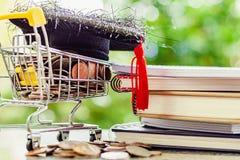 Tampão acadêmico quadrado na moeda do dinheiro no mini carrinho de compras ou pesca à corrica foto de stock