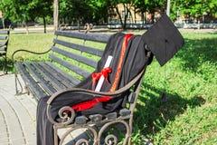 Tampão da graduação, chapéu com borla preta, envoltório com um grau de papel em um banco de parque fotografia de stock