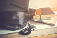 tampão da graduação, chapéu com papel do grau na graduação de madeira c da tabela Fotos de Stock Royalty Free