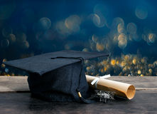 tampão da graduação, chapéu com papel do grau na tabela de madeira, li abstrato fotografia de stock