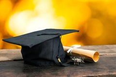 tampão da graduação, chapéu com papel do grau na tabela de madeira, li abstrato foto de stock